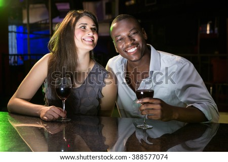 Couple smiling while having red wine at bar counter in bar - stock photo