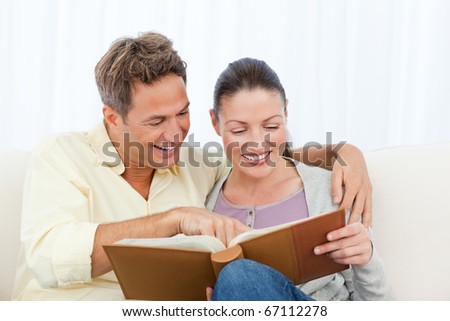 Couple smiling while looking at pictures on a photo album at home - stock photo