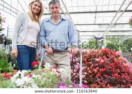 Couple smiling while pushing a trolley in garden centre