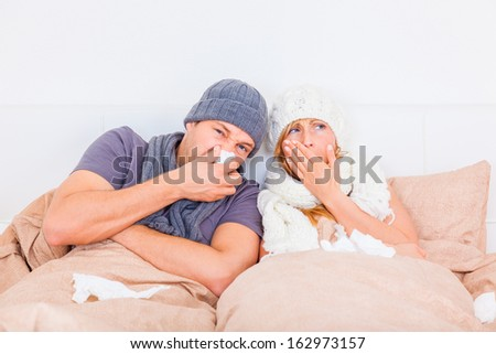 couple sneezing ill lying down