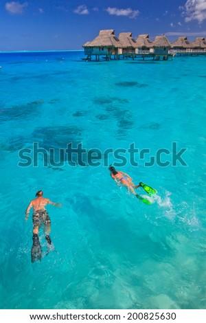Couple snorkeling in the blue lagoon,   Bora Bora, French Polynesia, South Pacific - stock photo