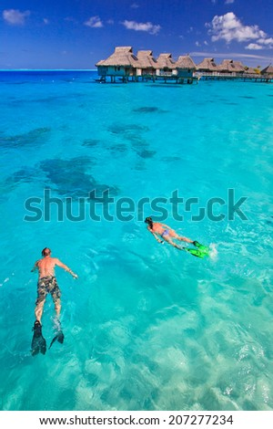 Couple snorkeling in the blue lagoon, Bora Bora, French Polynesia, South Pacific  - stock photo