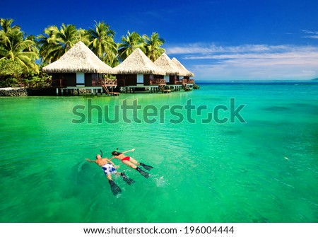 Couple snorkling in tropical lagoon with over water bungalows - stock photo