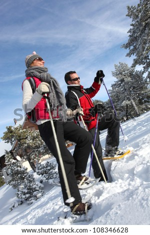 Couple snow-shoeing - stock photo