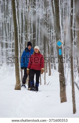 Couple snowshoeing in the forest after a winter snowstorm