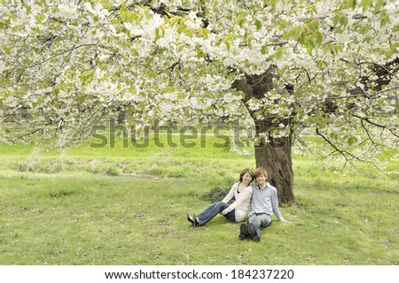Couple snuggles up under a cherry tree.