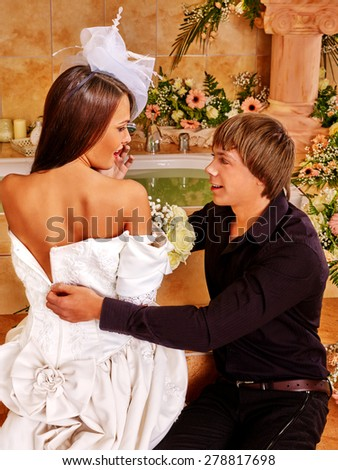 Couple spend wedding night  at luxury spa. Man helps relieve girl dress. - stock photo