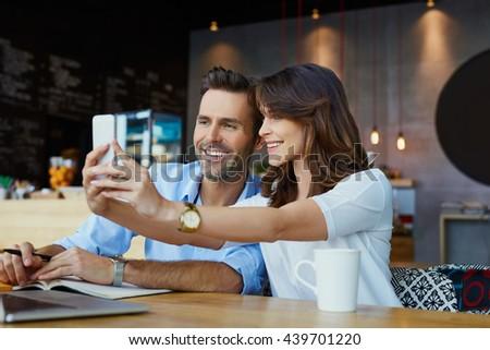 Couple spending time at coffee shop, having fun, taking selfie - stock photo