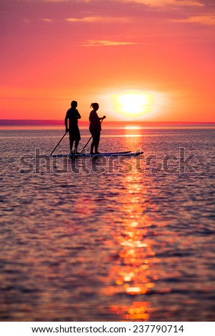Couple stand up paddle boarding at sunset - stock photo