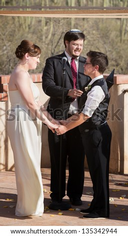 Couple standing and holding hands for wedding ceremony
