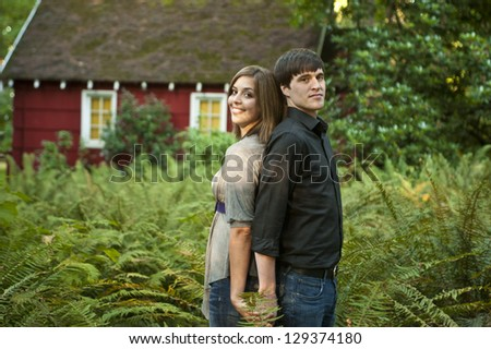 Couple standing back to back among ferns - stock photo