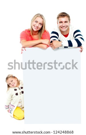 Couple standing behind blank white ad board while their daughter sitting on the floor - stock photo