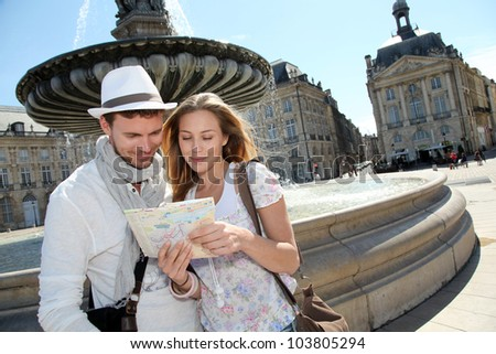 Couple standing by a fountain in Bordeaux with map - stock photo