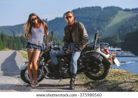Couple standing by a motorbike. Handsome man wearing leather jacket leather gloves and boots and young beautiful sexy woman wearing shorts. Summer day in the mountains. - stock photo
