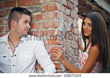 Couple standing by a stone wall - stock photo