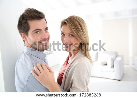 Couple standing in contemporary home - stock photo
