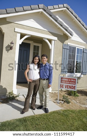 Couple standing in front of a new house