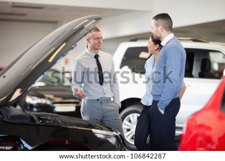 Couple standing in front of an open car engine in a car shop