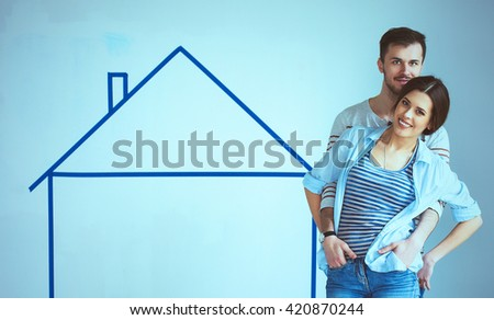 Couple standing in front of painted home on wall - stock photo