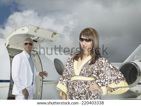 Couple standing in front of small jet - stock photo