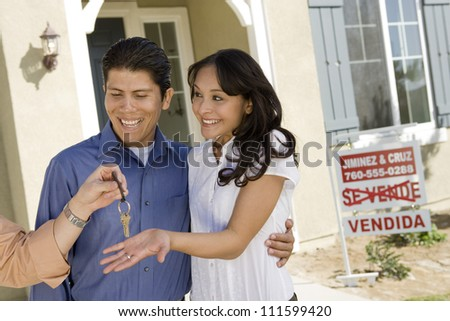 Couple standing in front of their new home - stock photo