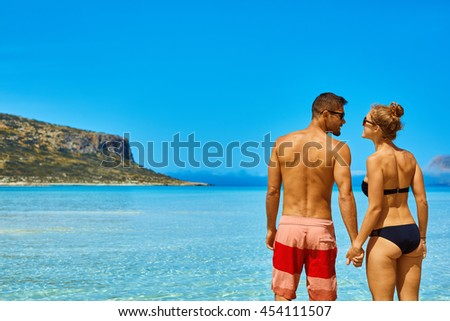 couple standing in the sea on the blue sky background