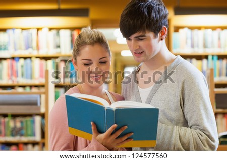 Couple standing looking at a book at the library - stock photo