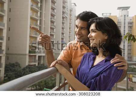 Couple standing on a balcony - stock photo