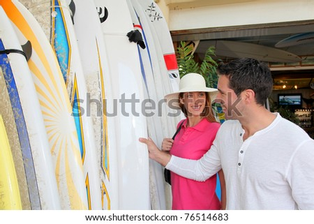 Couple standing on a surfshop - stock photo