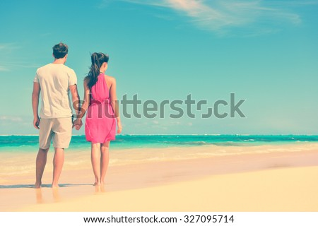 Couple standing on beach travel holding hands. Rear view of multiethnic romantic couple on shore. Young partners are watching sea. Tourists are enjoying their summer vacation at beach. - stock photo