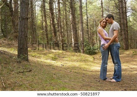 Couple standing on forest trail Hugging, side view - stock photo