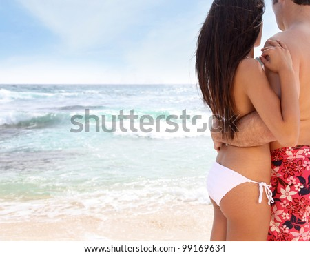 Couple standing on the beach, looking at the sea - stock photo
