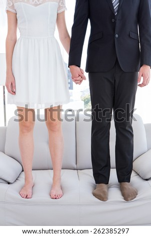 Couple standing on the couch on the living room