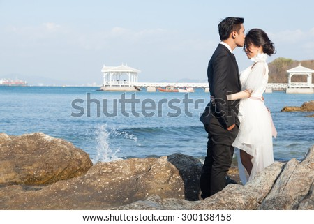 Couple standing on the rocks by the sea. Romantic couple standing near the ocean.