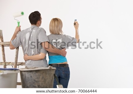 Couple standing together, embracing, holding paint brush and paint roller, painting wall.? - stock photo
