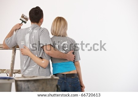 Couple standing together, embracing, holding paint brush, looking at white wall after painting.? - stock photo