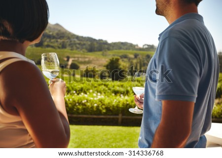Couple standing together holding glasses of white wine with vineyard in background. Man and woman standing outdoors drinking wine at winery. - stock photo