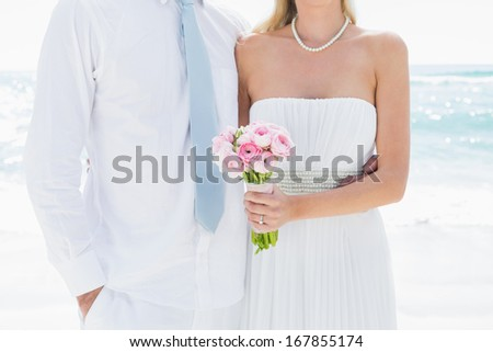 Couple standing together on their wedding day at the beach - stock photo