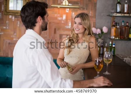 Couple standing with glass of wine in front of bar counter in restaurant