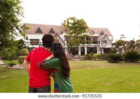 couple standing with their backs towards camera, couple standing against model house - stock photo