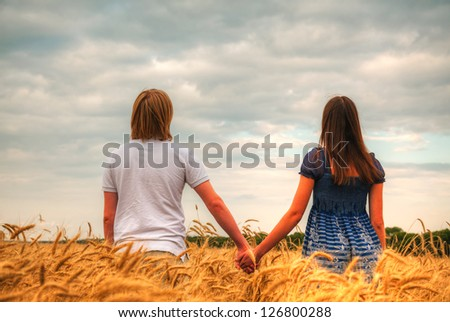 Couple staying at a wheat field at sunset time - stock photo