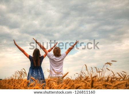 Couple staying with raised hands at a wheat field at sunset time - stock photo