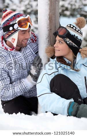 Couple stood by their chalet - stock photo