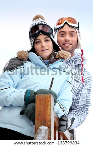 Couple stood in front of skiing holiday accommodation - stock photo