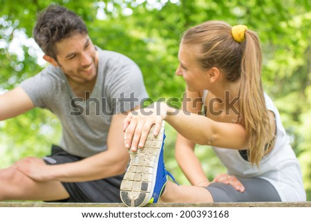Couple stretching legs after run outdoors - stock photo