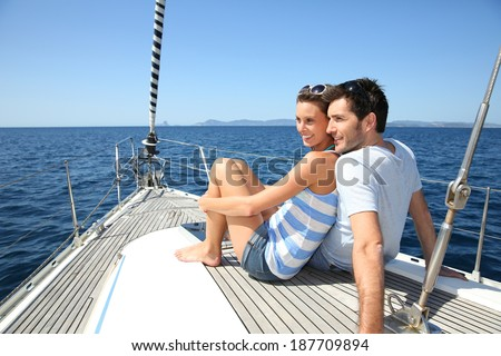 Couple stting on sailboat deck looking at sealine - stock photo
