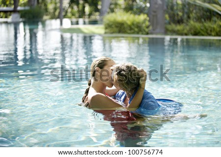 Couple submerged into a swimming pool, kissing and hugging while dressed. - stock photo