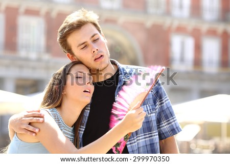 Couple suffering summer heat and fanning with a fan - stock photo