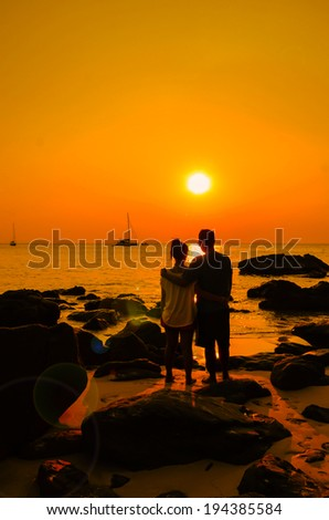 Couple sweetheart standing on a rock by the sea and watching sunset.
