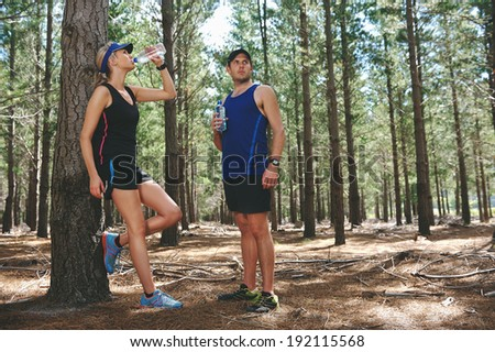 Couple take rest to drink water after running marathon on trail - stock photo